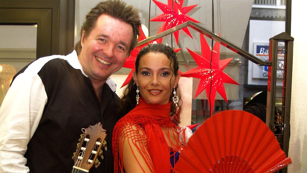 Spanischer Sänger und Gitarrist René el Payo mit seiner spanischen Gitarre und einer Flamencotänzerin mit Fächer bei einer Weihnachtsveranstaltung in einem Modehaus
