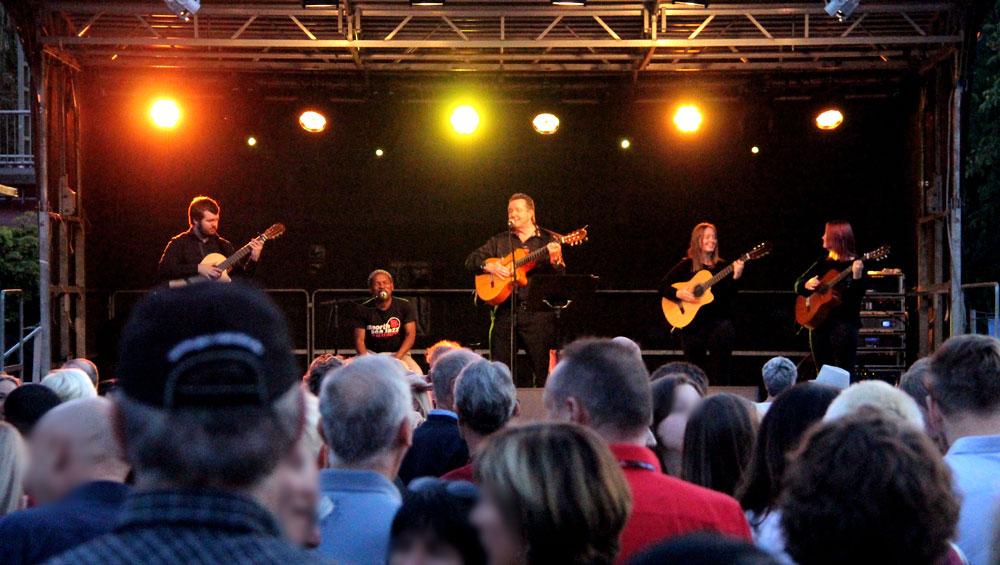 Die spanische Gipsy Kings Coverband Gipsy FamilyLos Payos auf einer beleuchteten Bühne Abends bei einem Stadtfest mit Publikum vor der Bühne