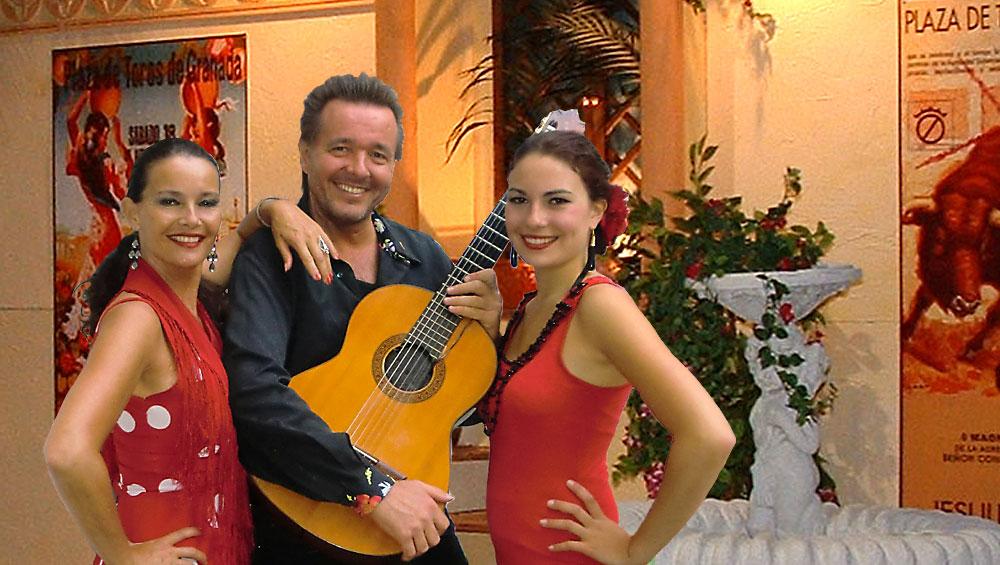 Spanischer Sänger und Gitarrist René el Payo mit zwei Flamencotänzerinnen vor einer spanischen Kulisse
